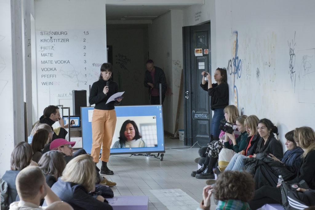In einem Raum in der Hochschule für Grafik und Buchkunst Leipzig sitzt eine Gruppe Menschen. In ihrer Mitte befinden sich Agnieszka Roguski und ein Bildschirm, auf dem die Kuratorin Binna Choi zu sehen ist. Der Skype-Workshop hat 2019 im Rahmen des Symposiums und der Programmwoche Show and Try Again stattgefunden.