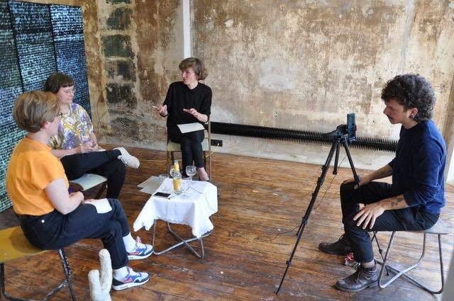 Im Ausstellungsraum von MMS Offspace Bremen sitzen vier Personen. Anlässlich der Ausstellung Anisotropie im Frühjahr 2020 interviewte Sarah Maria Kaiser die Künstler:innen Irene Strese und Barbara Proschak. Eine Person filmt das Gespräch. Das Foto hat Rebekka Kronsteiner aufgenommen.
